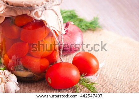 Canned tomatoes with garlic and herbs in a glass jar on the wooden table - stock photo