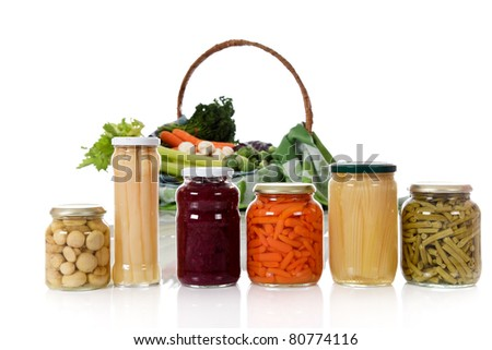 Canned vegetables in jars versus fresh vegetables in basket. Focus on jars. Healthy eating concept. Studio shot. White background. Copy space. - stock photo