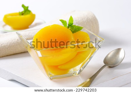 Canned yellow peach in glass bowl - stock photo