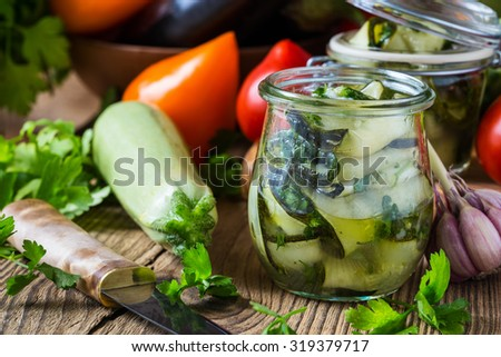 Canned zucchini and fresh vegetables. Sliced zucchini with parsley and garlic, homemade vegetables preserves in glass jar - stock photo