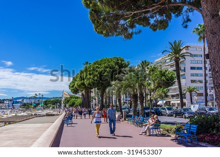CANNES, FRANCE - JULY 7, 2014: Cannes cityscape. Cannes - a resort in southern France: many flowers and palm, luxury boutiques and restaurants, cafes, luxurious hotels - all for leisure travelers. - stock photo