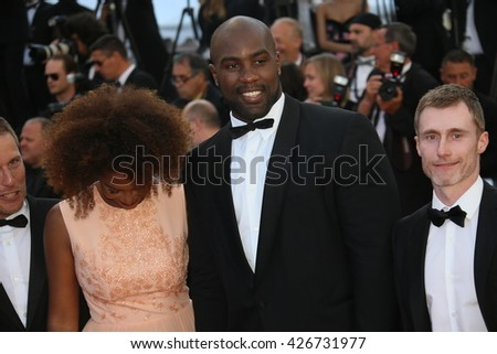 CANNES, FRANCE - MAY 21: Teddy Riner and his partner Luthna Lors attend the 'Elle' Premiere during the 69th annual Cannes Film Festival at the Palais des Festivals on May 21, 2016 in Cannes, France. - stock photo