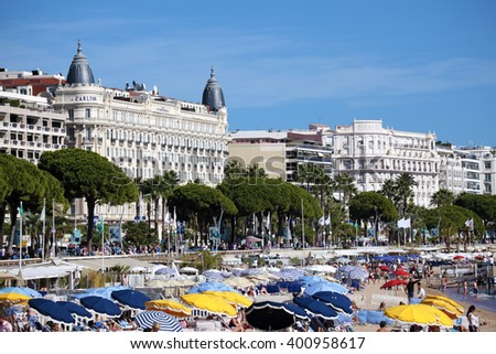 Cannes, France - September 18, 2013: Busy crowded beach in front of the Carlton International Hotel situated on the croisette boulevard in Cannes, France  - stock photo