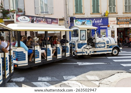 CANNES, FRANCE - SEPTEMBER 8, 2014: The little train of Cannes travels through the narrow streets of the old town of Cannes and it is a good way of having a quick view of the city.  - stock photo