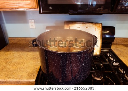 Canning jars boiling in  water to kill any bacteria and sealing process. - stock photo