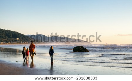 CANNON BEACH, OR-OCT 28, 2013: A family walking along the water's edge at Cannon Beach, a destination on the Oregon coast famous for its natural beauty and wide sandy beaches. Sunset. - stock photo