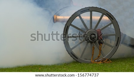 Cannon with smoke after firing - stock photo