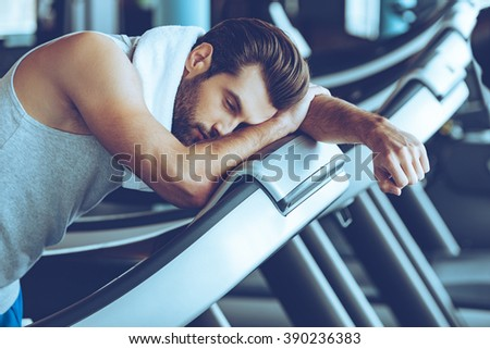 Cannot run anymore. Side view of young man in sportswear looking exhausted while leaning on treadmill at gym - stock photo