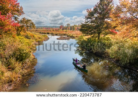 canoe flowing down a river in the fall - stock photo