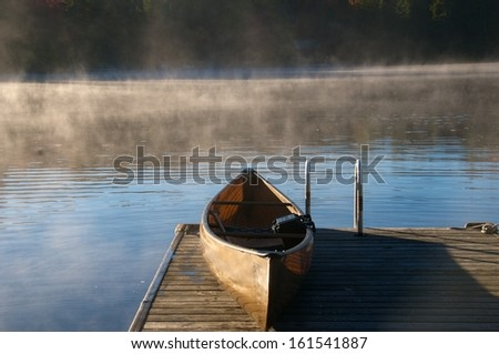 Canoe rests on the dock on an early cool Adirondack morning - stock photo