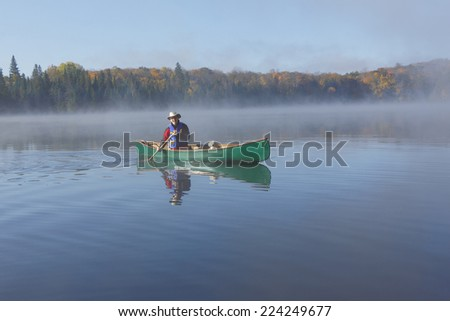 Canoeist Paddling a Green Canoe on a Misty Autumn Lake - Ontario, Canada - stock photo