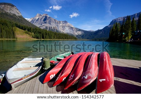 Canoes beside  Emerald Lake with mountain and blue sky as background, Yoho National Park, Canadian Rocky Mountain, Golden, British Columbia, Canada - stock photo