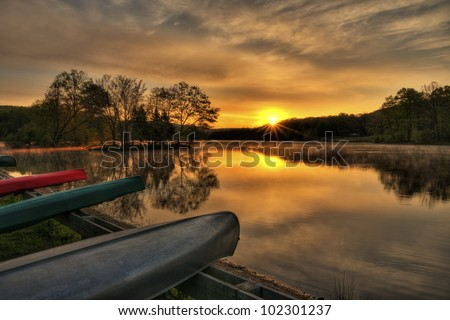 Canoes moored by a beautiful lake at sunrise. - stock photo
