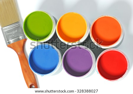 Cans of different colors and paintbrush over light background - stock photo