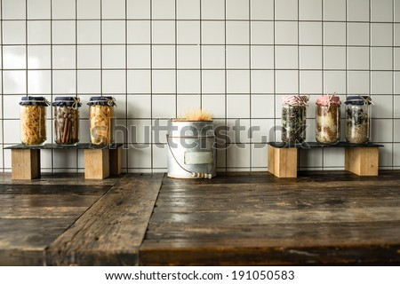Cans with different grocery items on wooden kitchen table - stock photo