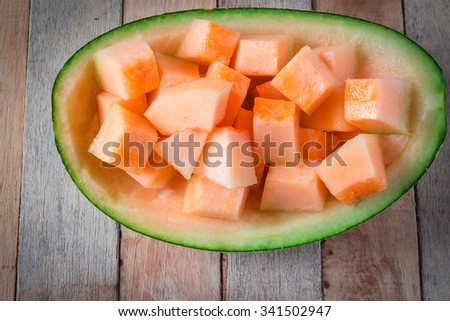 Cantaloupe, cut into pieces, put on a wooden background. - stock photo
