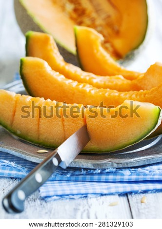 Cantaloupe melon slices on metal rustic plate - stock photo