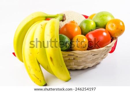 Canteloupe, lime; orange, tomato, apple, tangerine, tangelo, bananas in basket against white background. - stock photo