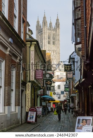 CANTERBURY, UK - JAN 23, 2015: A view of Canterbury Cathedral at the bottom of the cobbled Butchery Lane. Most of the original buildings on the right hand side were damaged in the bombing of WW2 - stock photo