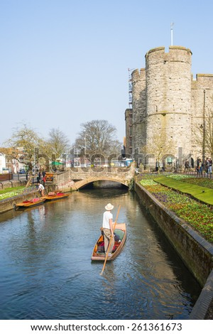 CANTERBURY, UK - MAR 17, 2015: Tourists enjoy a punt along the river stour and views of Canterbury along the Westgate Gardens Riverwalk.This site has been a public space since the Middle Ages. - stock photo