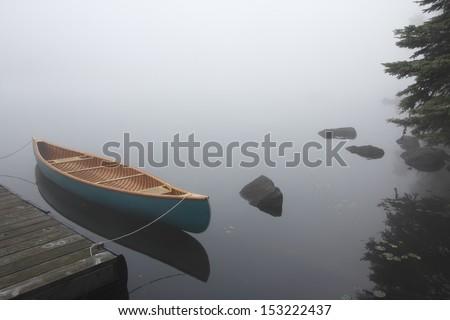 Canvas Cedar Canoe Tied to a Dock on a Misty Morning - Haliburton, Ontario - stock photo