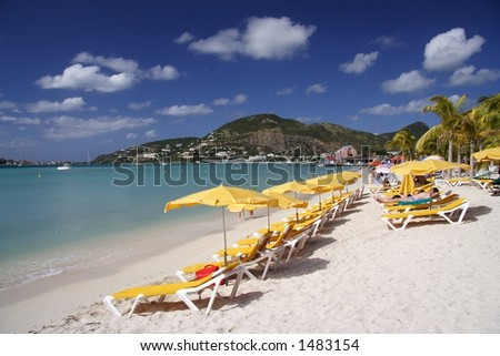 Canvas chairs and sun shades at a beautiful caribbean beach - stock photo