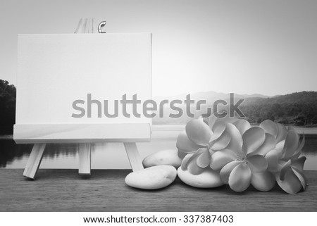 canvas frame and pink plumeria on blue lake background with sun light ,black and white tone - stock photo