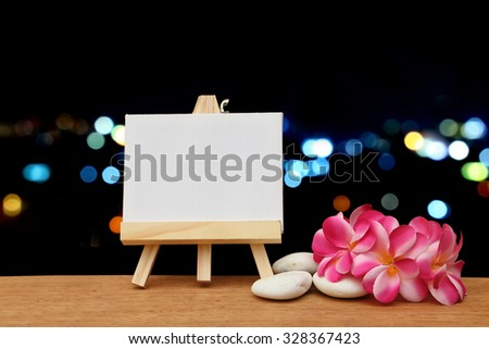 canvas frame and pink plumeria on  blur bokeh light in city background - stock photo