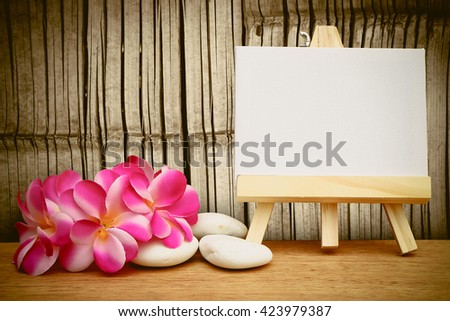 canvas frame and pink plumeria with old bamboo wall background - stock photo
