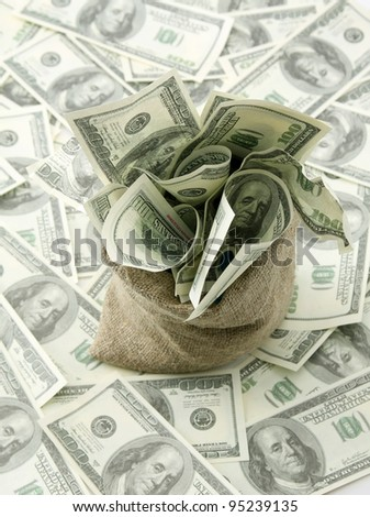 Canvas money sack with one hundred dollar bills - stock photo