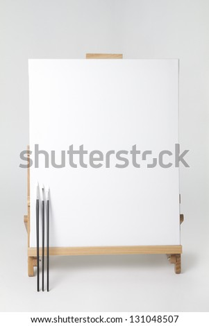 Canvas on Easel - Clipping Path full shot of canvas on easel with 3 paint brushes leaning up against canvas. Clipping path is of canvas only. place your image on canvas with clipping mask - stock photo