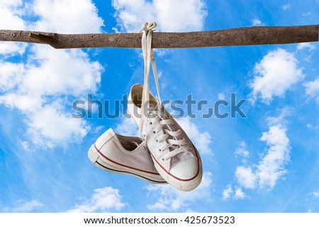canvas shoes hanging on brunches (isolated with clipping path ).with blue sky background - stock photo