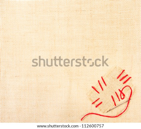 Canvas with stitched patch and needle over burlap background. Sackcloth label with copy space - stock photo