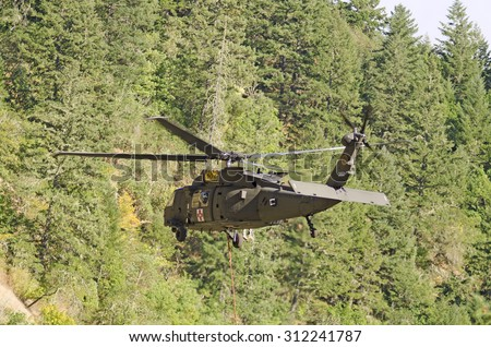 Canyonville, OR, USA - August 06, 2015: Oregon National Guard UH-60 Blackhawk Type 1 helicopter comes in for a fill of its water bucket at a wildland fire in Oregon. - stock photo