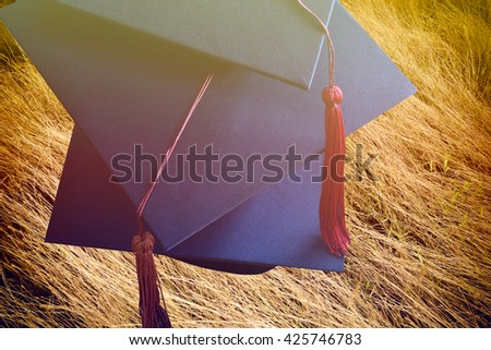 Cap, gown graduates on grass background - stock photo