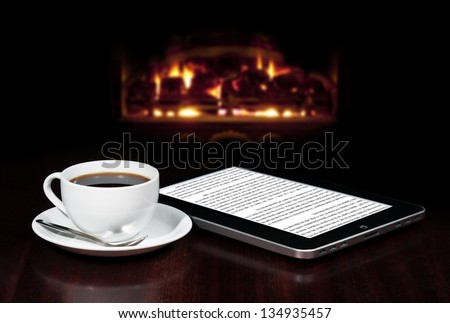 Cap of coffee and tablet on the table top with fireplace in the background. - stock photo