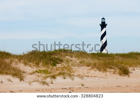 Cape Hatteras Lighthouse towers over beach dunes of Outer Banks island near Buxton, North Carolina, US - stock photo