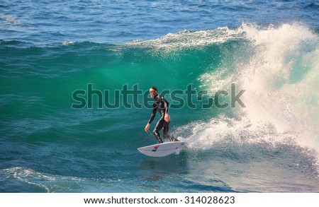 CAPE SOLANDER, AUSTRALIA, AUGUST 9, 2015; a male surfer, catching and surfing the breaks off Cape Solander near Sydney on a beautiful and sunny winter day. - stock photo