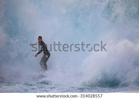 CAPE SOLANDER, AUSTRALIA - AUGUST 27, 2015; Surfer riding through a massive wave as it crashes around him at Cape Solander - stock photo