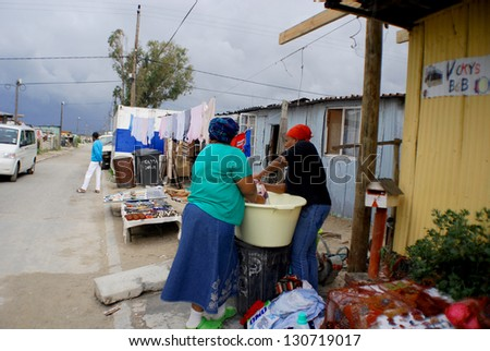 CAPE TOWN SOUTH AFRICA MAY 23: Women wash their clothes in Khayelitsha township on may 23 2007 in Cape Town South Africa It is reputed to be the largest and fastest growing township in South Africa - stock photo