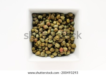 capers in white dish isolated on white background - stock photo