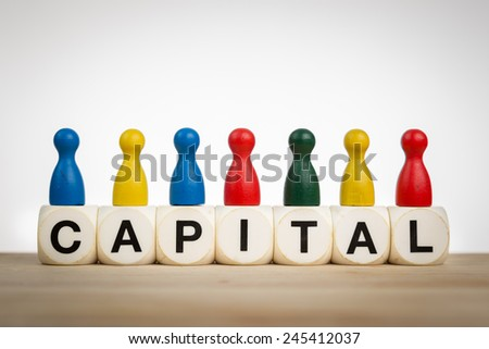 Capital concept: Pawns in different colors on top of toy dice - stock photo