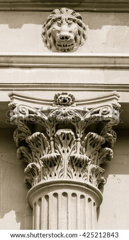 Capital of corinthian column with sculpture of lion head above vertical black and white photography split toning sepia tone - stock photo