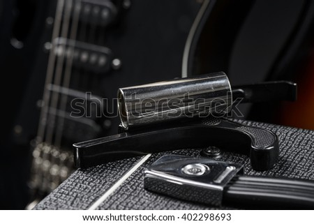 Capo in a foreground on the top of amp. Blurred electric black guitar in a background. - stock photo