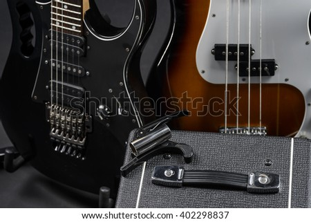 Capo is in the focus of camera, while the other musical instruments are not. Electric and bass guitars of black and brown with white colors. The top of an amp. - stock photo