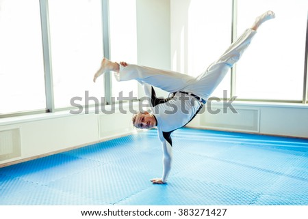 Capoeira performer showing his technical skill while dancing in a fight club - stock photo