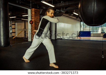 Capoeira performer showing his technical skill while practising with punching bag in a fight club - stock photo