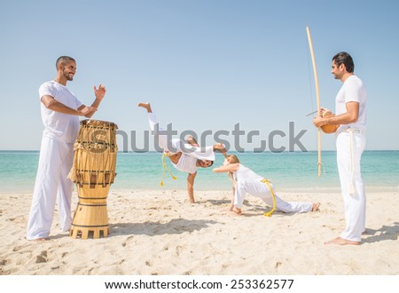 Capoeira team training on the beach - Martial arts athletes performing stunts while two men play music - stock photo