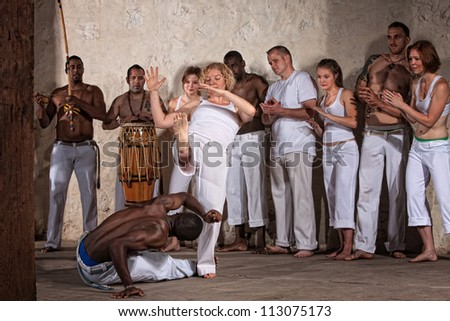 Capoeria experts kick and evade with group in background - stock photo