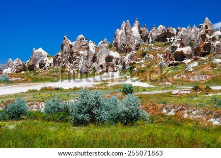 Cappadocia, Central Anatolia in Turkey. Desert landscape with ancient rock carved houses in Goreme turkish Kapadokya region in Asia Minor. - stock photo